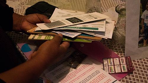 Sofia Aristeo Serdan looks through Prospera Program paperwork that sits on her dining room table. (Photo by Danielle Quijada)