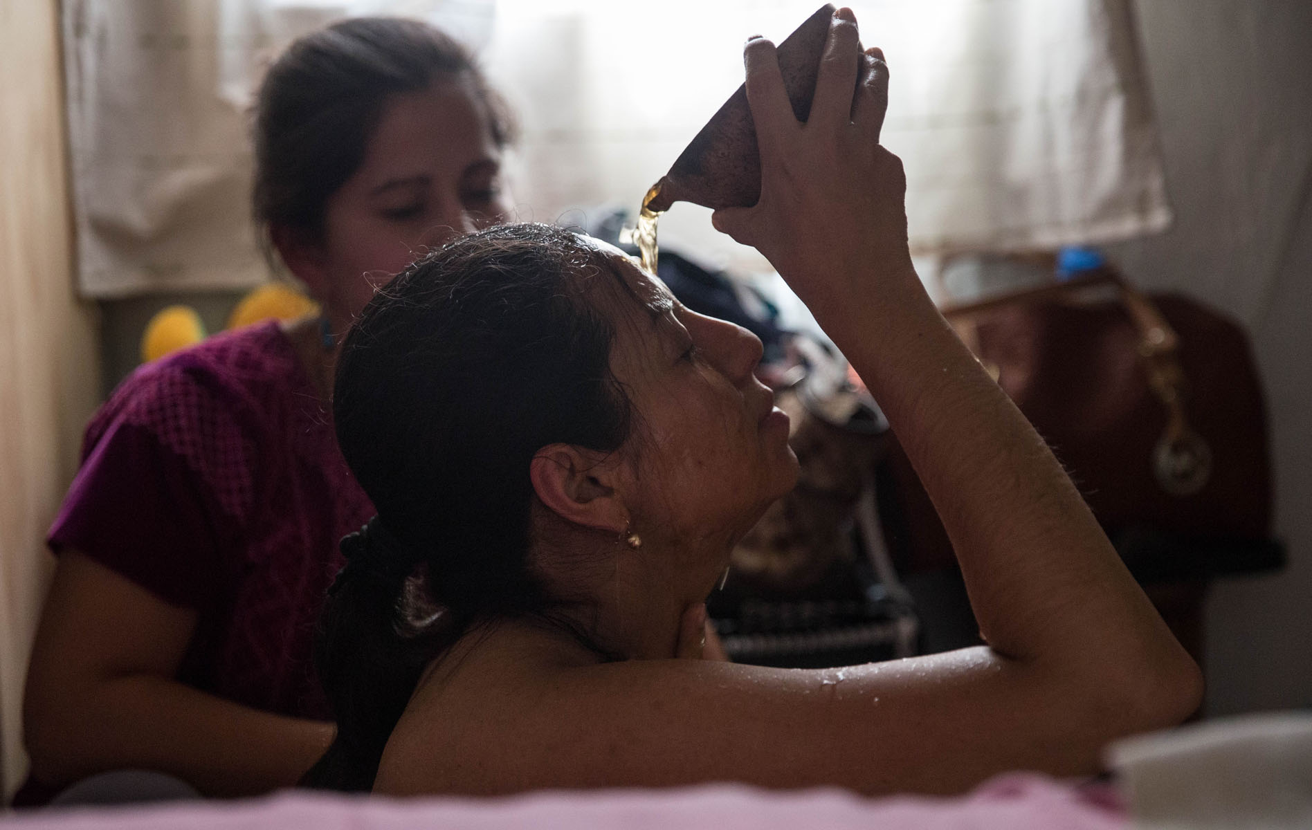 Dia Cruz pours water over her head to ensure that every part of her body is cleansed during the ceremony.