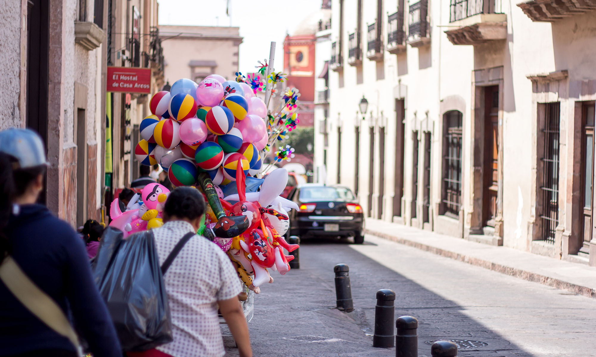 A street vendor moves merchandise along a sidewalk near the city center of Santiago de Querétaro in Mexico.