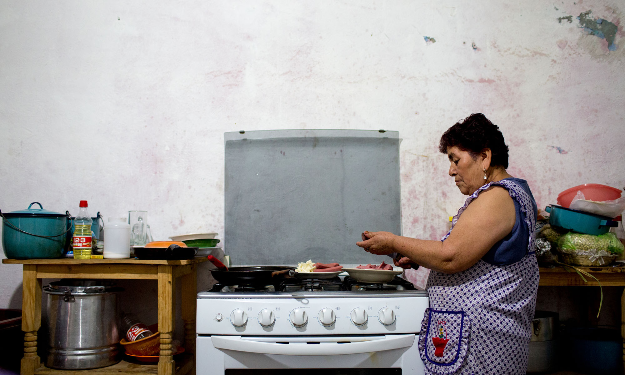 """Rodriguez makes lunch for her family in the town of Caleras, Mexico. Her son has been in the United States for over 20 years, in San Antonio. He is an undocumented worker and she worries for his safety after seeing news stories and hearing from people who have been deported. She doesn't want him to be separated from his daughters. He first left at age 16, came back home then left for good two years later. """"He always had that idea that he should help us. We work to survive. That's why he left. He said, 'I'm leaving so I can help you,'"""" Rodriguez said. (Photo by Courtney Pedroza/Cronkite Borderlands Initiative)"""