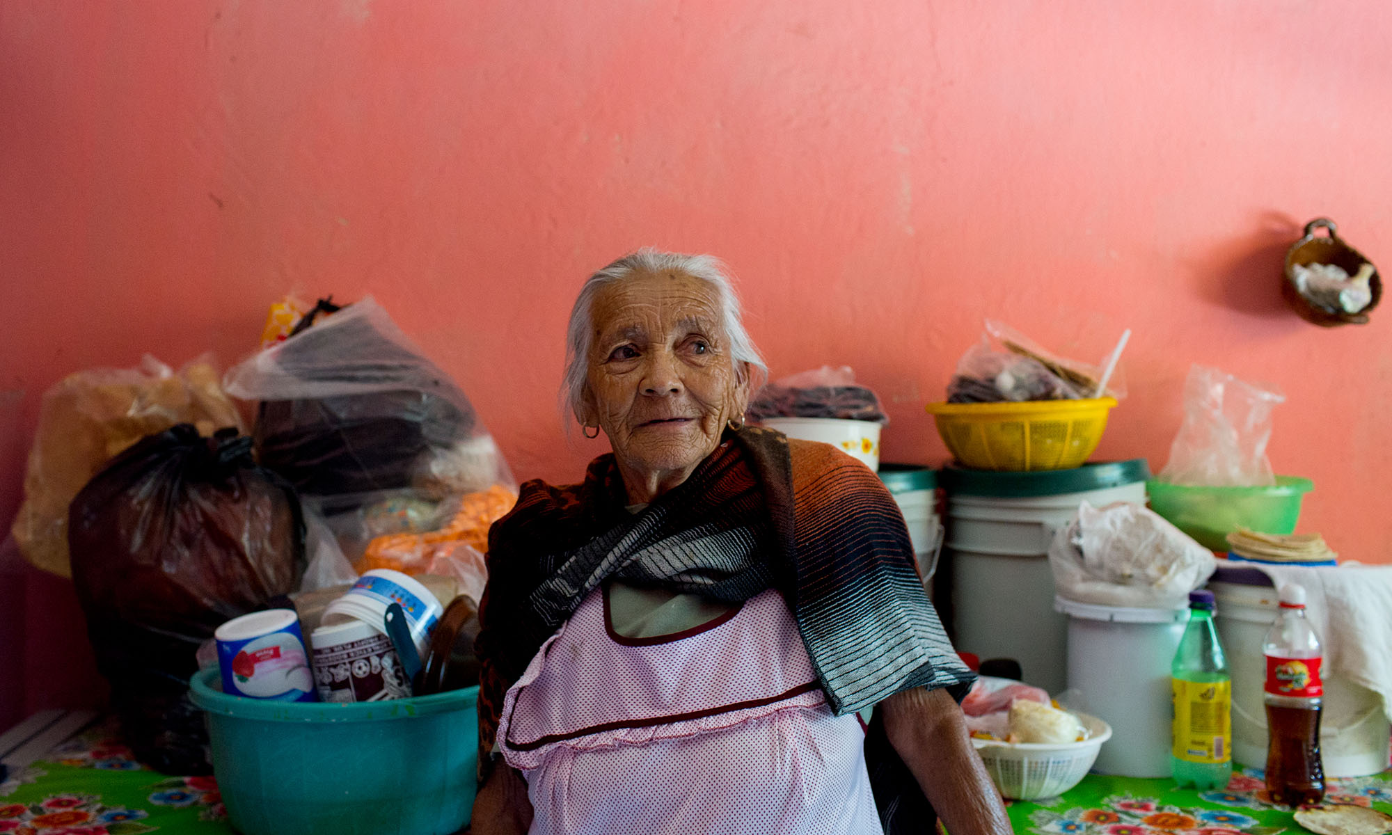 """Rojas in her kitchen. She does no longer works and she and her husband rely heavily on remittances from their children, in addition to a little government support. Her children crossed the border in the 1980s, became legal, documented immigrants during the Reagan administration and are now U.S. citizens with their own American grandchildren. Rojas has about 15 grandchildren and great-grandchildren who are U.S. citizens, including one who did military service. Because the family can cross the border legally, they are able to visit and were home at Christmas, but Rojas wishes she could see them more. """"One day I'm going to die, one day, and I'm not going to see my children anymore,"""" Rojas said. (Photo by Courtney Pedroza/Cronkite Borderlands Initiative)"""