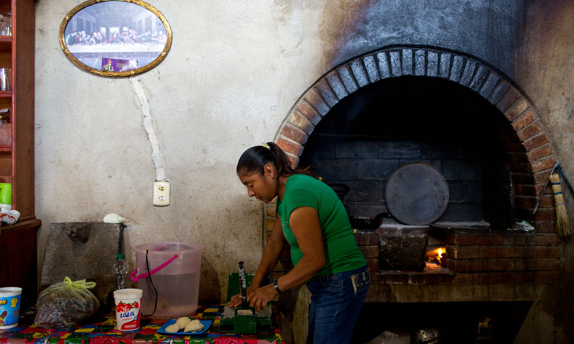 """Martinez makes tortillas in her kitchen. Since her daughters no longer help support her in Tancama, Mexico - an area with few job opportunities - she works as a chef for tourists in a nearby eco-lodge. Martinez doesn't remember when her children left to find work in the U.S., some time between five and 10 years ago. Because they are undocumented, they can't find work easily. She said she hasn't spoken to them in eight to 12 months. When asked if she missed her daughters she said, """"Of course. A lot… I can't see them here because they can't come back and forth."""" (Photo by Courtney Pedroza/Cronkite Borderlands Initiative)"""