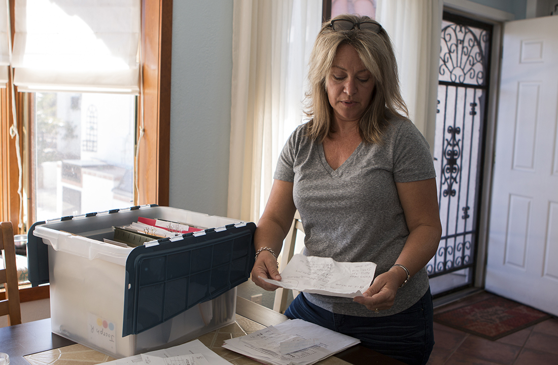 Tucson resident Susan Romeo keeps a crate full of bills from treatment centers to fight her son's addiction. (Photo by Kristiana Faddoul/Cronkite News)