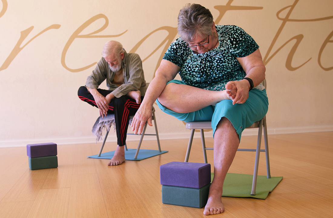 RJ Davis (right) and Geoffrey Davis take a chair yoga class at Inner Vision Yoga Studio in Chandler. (Photo by Ao Gao/Cronkite News)