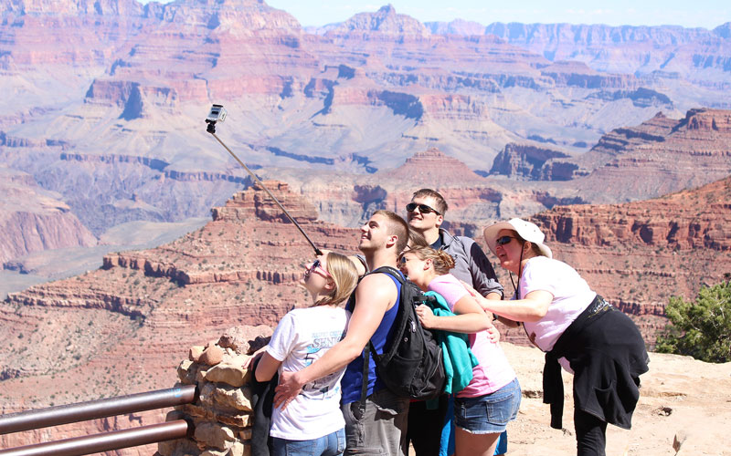 Tourists pose for a selfie in Grand Canyon National Park. The Escalade project would aim to bring in more tourist revenue. (Photo by Sophia Kunthara)