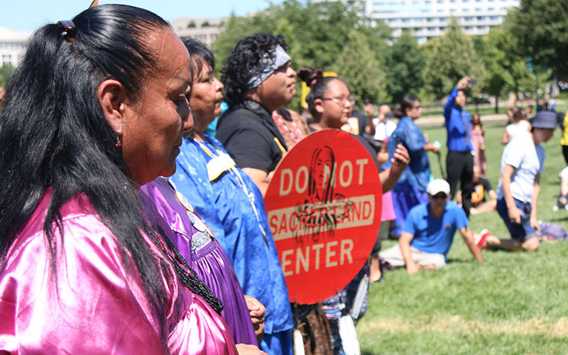 """San Carlos Apache tribe members listen to the """"war song"""" that began their protest at the Capitol over the proposal to allow mining at Oak Flat. (Photo by Jamie Cochran)"""