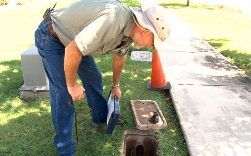 A water conservation specialist examines a water meter.