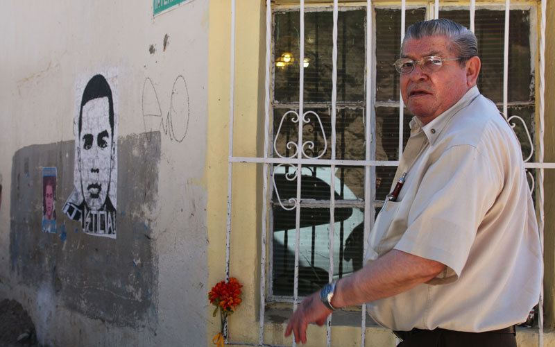 Sanchez shows posters on the side of his home above the exact spot where Rodriguez died.