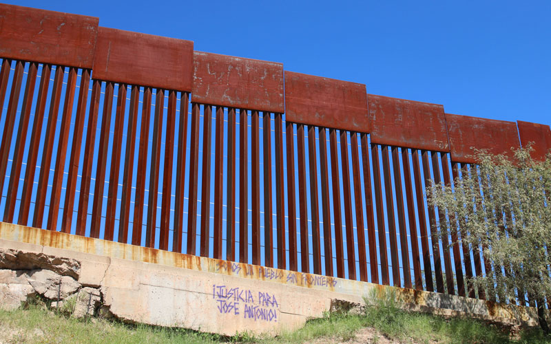 "Purple grafitti with the words ""justice for Jose Antonio!"" marks part of the border fence on the Mexico side."