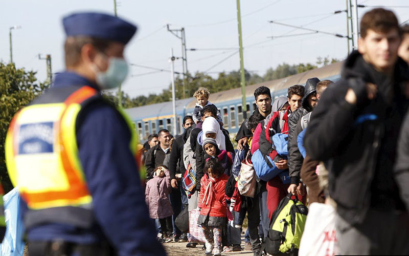 As police look on, migrants line up to board a train at the railway station in Zakany, Hungary, on Oct. 1. (Photo by Bernadett Szabo/Reuters)