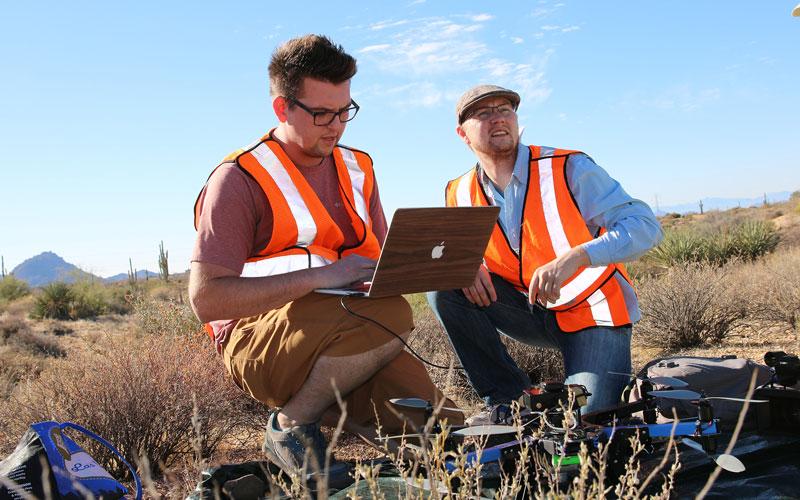Researchers Ben Stinnett and Brenton Scott pilot the drone over the desert landscape. (Photo by Ty Scholes/Cronkite News)