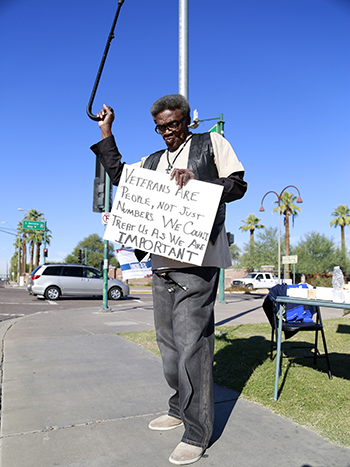 Wallace J. Brown Sr. waves his cane at honking cars passing by in support of a veterans rally at the Phoenix VA Medical Center on Monday, Nov. 9, 2015.  He said he had hoped President Obama's visit back in March would have led to improvements in patient care. (Photo by April Morganroth/Cronkite News)