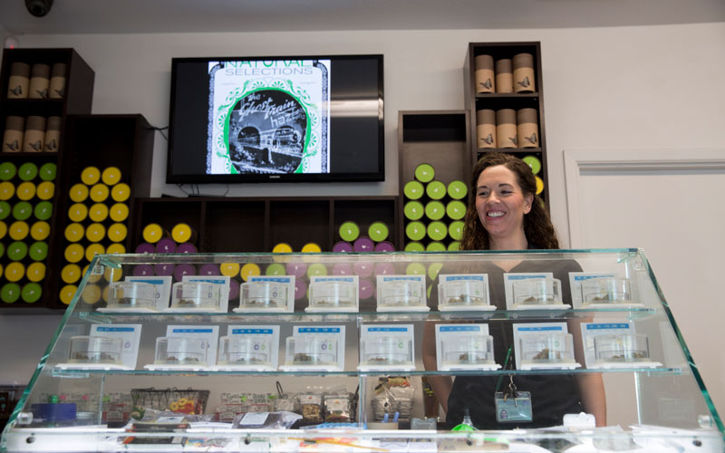 Blythe Huestis, manager of Natural Selections,  looks through the display case in her Arizona facility. The dispensary carries a multitude of cannabis products from flower or bud to cookies and infused tea. (Photo by Sean Logan/News21)