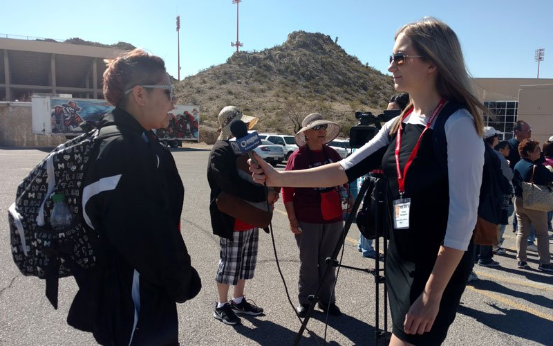 Chloe Nordquist interviews an attendee at the University of Texas at El Paso Sun Bowl before the livestream of Pope Francis' Mass in Ciudad Juárez. (Photo by Molly Bilker/Cronkite News)