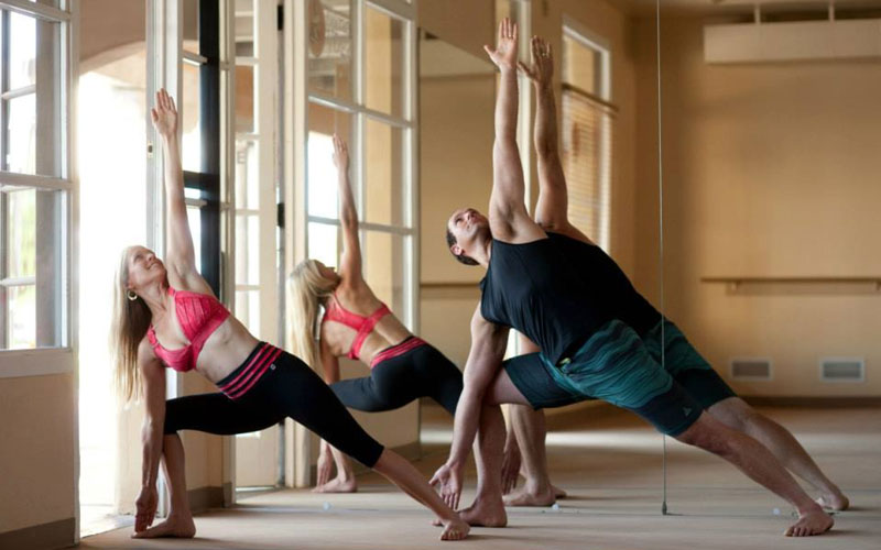 Bikram Yoga Tempe owners Ben and Elaina Zorensky practice in their studio. (Photo courtesy Bikram Yoga Tempe)