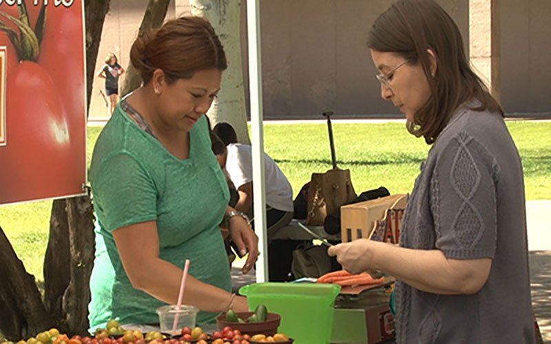 A shopper makes a purchase at one of the stands at the Capitol Farmer's Market.