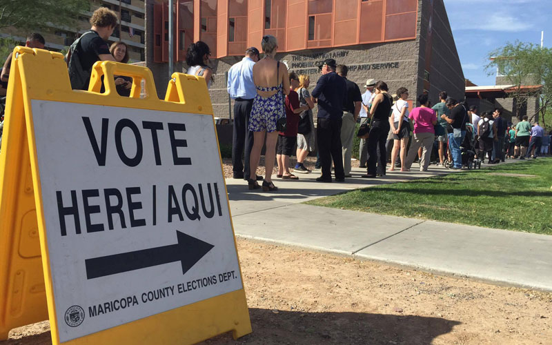 People line up to vote outside the Salvation Army's Citadel Corps polling place in downtown Phoenix on Tuesday, March 22. (Miguel Otárola/Cronkite News)