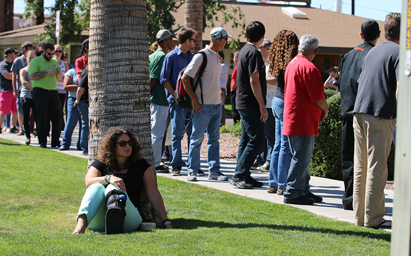 Leslie Sonnenklar takes a break while other voters hold her place in line at the Salvation Army Phoenix Citadel Corp. in downtown Phoenix. She had been waitng for 45 minutes Tuesday morning. (Photo by Grecia Drabos/Cronkite News)