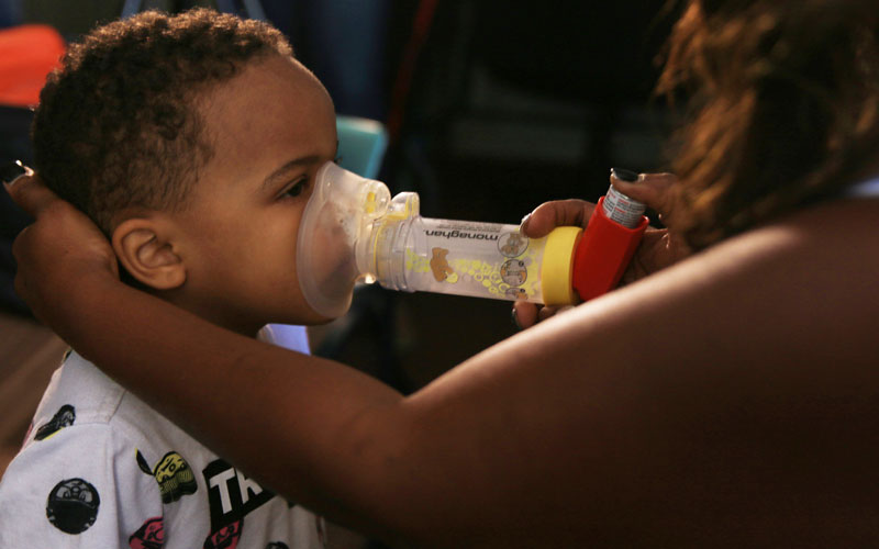 Lassandra Scott helps her four-year-old son, Zaviyon, use his inhaler just seconds after he was wheezing. (Photo by Alejandra Armstrong/Cronkite News).