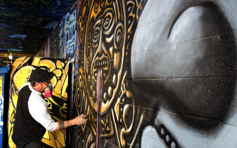 Valley artist Carlos Rivas, 36, works on a portion of a mural in downtown Phoenix.
