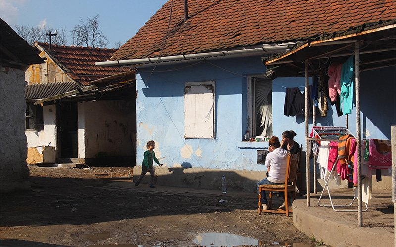 A Roma girl runs to two women as they sit and talk in one of the Roma neighborhoods of Sajókaza, Hungary.