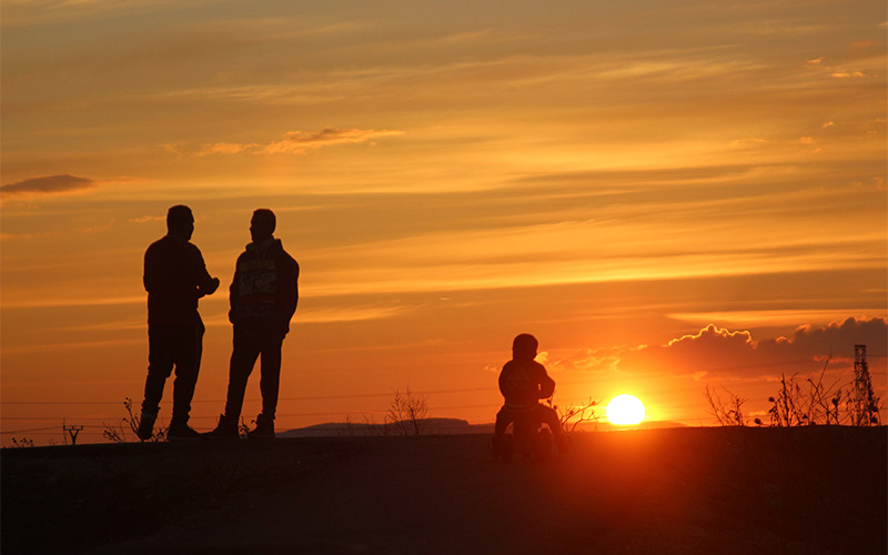 Two men and a toddler are silhouetted against a sunset on a hilltop over a Slovakian Gypsy ghetto. (Photo by Emily L. Mahoney)