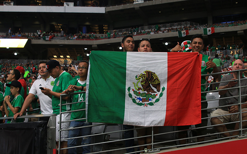 Supporters of the Mexican National Soccer Team pose with the Mexican flag just before the start of the game.