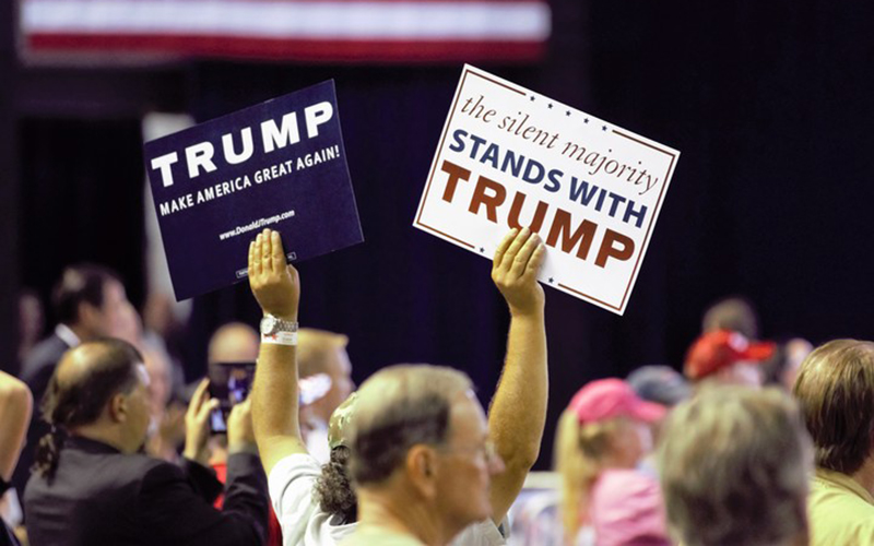 Trump supporters wave signs during his June 18 rally. (Photo by Selena Makrides/Cronkite News)