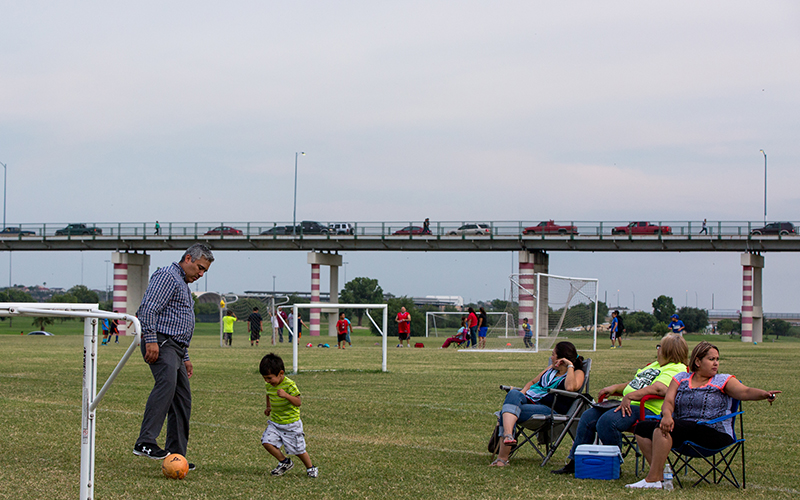 Calai Hernández (third from right) watches her son's soccer team practice at Shelby Park in Eagle Pass. Behind them is the International Bridge that connects Eagle Pass Texas to Piedras Negras, Coahuila.