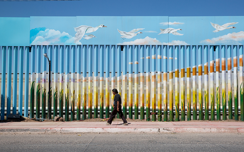 A man walks past the painted border fence in Agua Prieta, Mexico, in July 2015. (Photo by Cronkite News)