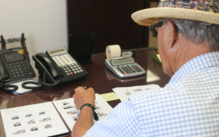 Farmer Doug Mellon, seen sitting at his desk, has witnessed the evolution in migrant labor policy throughout several decades in the agricultural industry. (Photo by Socorro Carillo/Cronkite News)