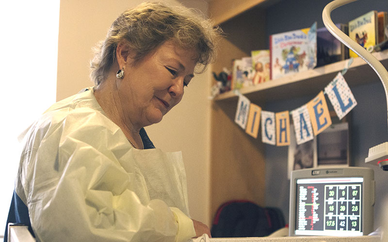 Diane Minton looks over her grandson at the Phoenix Children's Hospital. (Photo by Christopher West/Cronkite News)