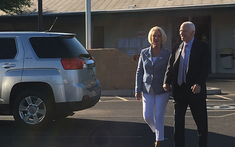 Republican Sen. John McCain and his wife, Cindy,  walk out to greet supporters after voting in the Arizona primary election. The veteran lawmaker faces Kelli Ward and three other opponents in the primary. (Photo by Mindy Riesenberg/Cronkite News)