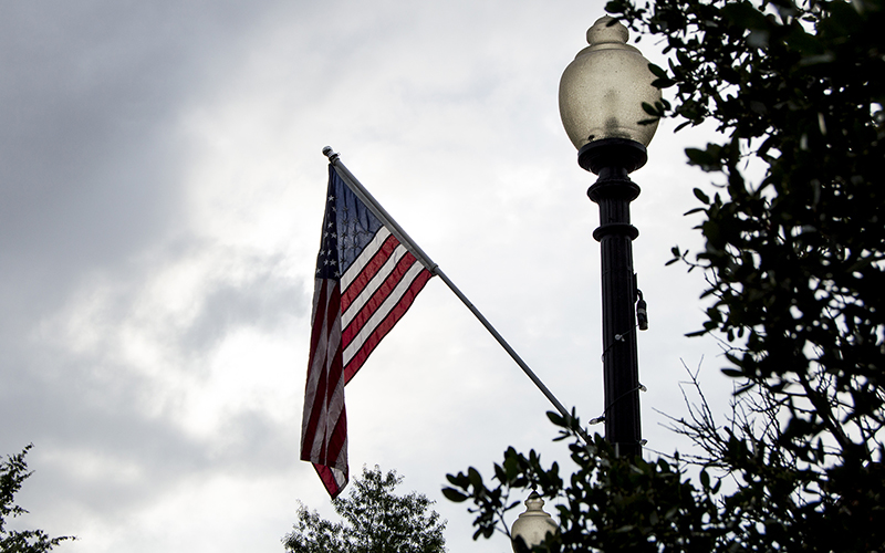 The sun breaks through the clouds, shining through an American flag on People Street in Fayetteville, North Carolina, outside Fort Bragg. (Photo by Michael Olinger/News21)