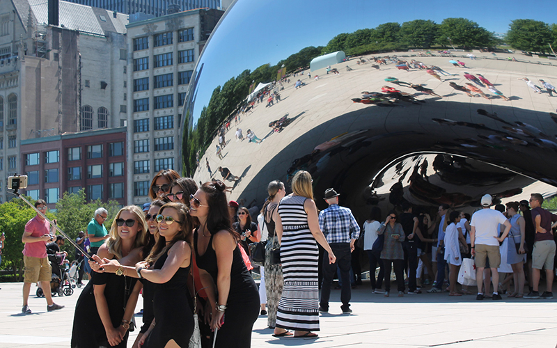 A group of millennials take a selfie in front of Cloud Gate, commonly known as