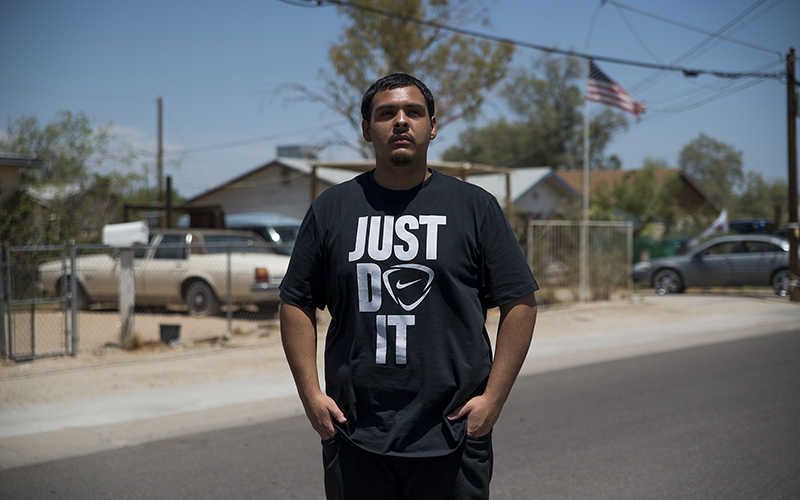 David Castorena, 24, of Chandler, Arizona, stands in the street of a small, largely Latino community in Arizona where he attends church. Castorena said he does not plan to vote in the November election because he thinks Donald Trump will win either way. (Photo by Roman Knertser/News21)