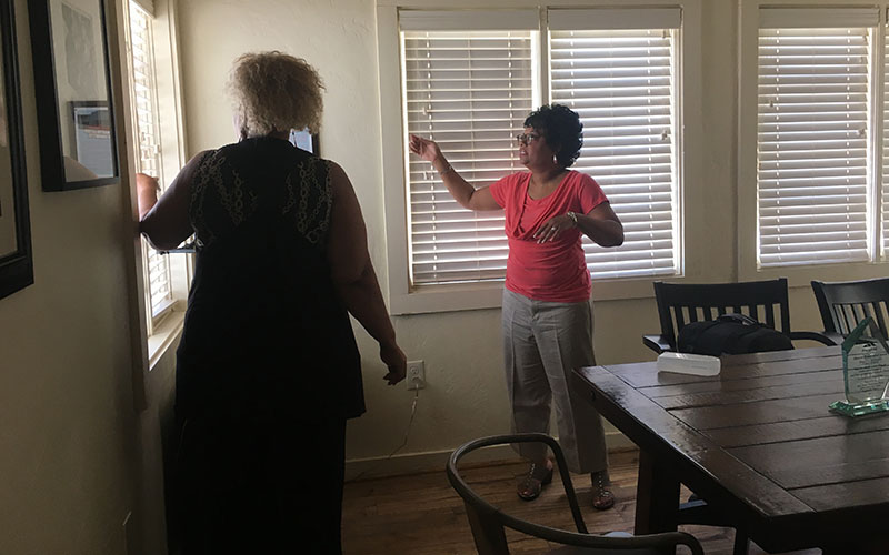 Ladina Willis (left) and Angela Booker of the Mesa MLK Committee joke around in the house of Mesa's first practicing African-American doctor, which they currently lease from the city and hope to turn into a museum. (Photo by Elizabeth S. Hansen/Cronkite News)