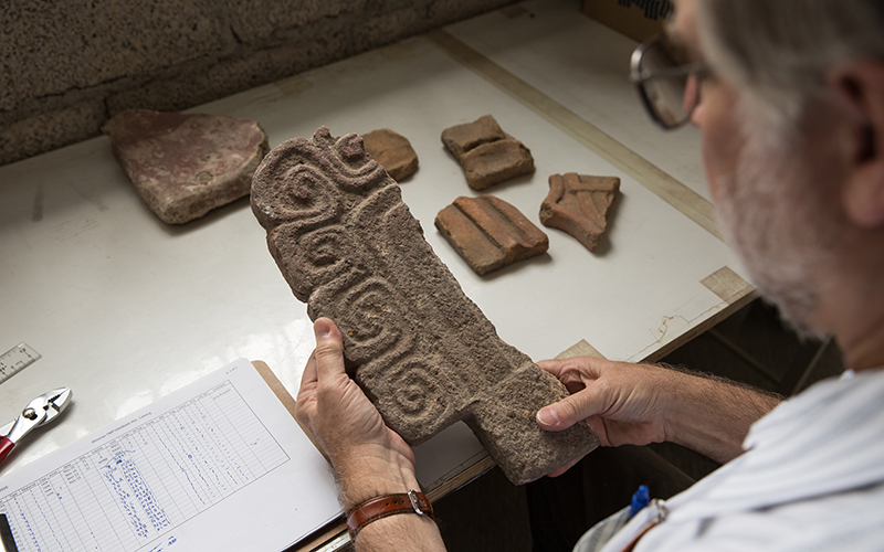 Professor Mike Smith looks at part of an Almena at the ASU Teotihuacan Research Laboratory. (Photo by Ken Fagan/ASU Now)