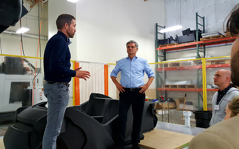 Steve Case (right) and Local Motors CEO John B. Rogers Jr. discuss the Phoenix company's production methods. (Photo by Gavin Maxwell/Cronkite News)