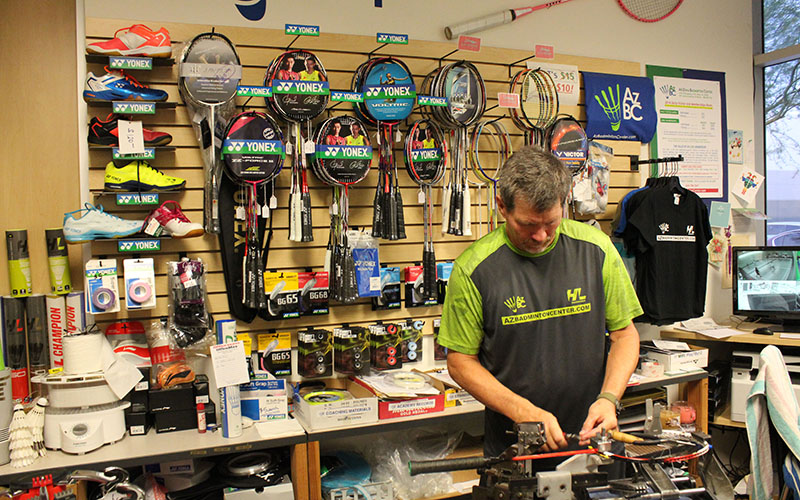 "In the pro shop at the Arizona Badminton Center, Guy Chadwick restrings a racket for Alex Bimes, who referred to Chadwick as, ""the godfather of badminton here in Arizona, and really the southwest."" (Photo by Michael Boylan/Cronkite News)"