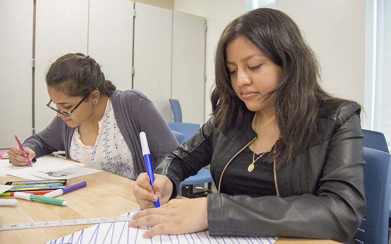 Alba Leon (left) and Emyli Hinojosa are in Phoenix Coding Academy's first class of 90 students who will graduate knowing how to build apps, collaborate in teams, develop video games and program robotic arms. (Photo by Ally Carr/Cronkite News)