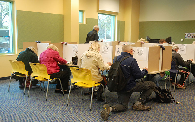Voters exercise their right to vote at the polls (Photo by KOMUnews via Creative Commons)