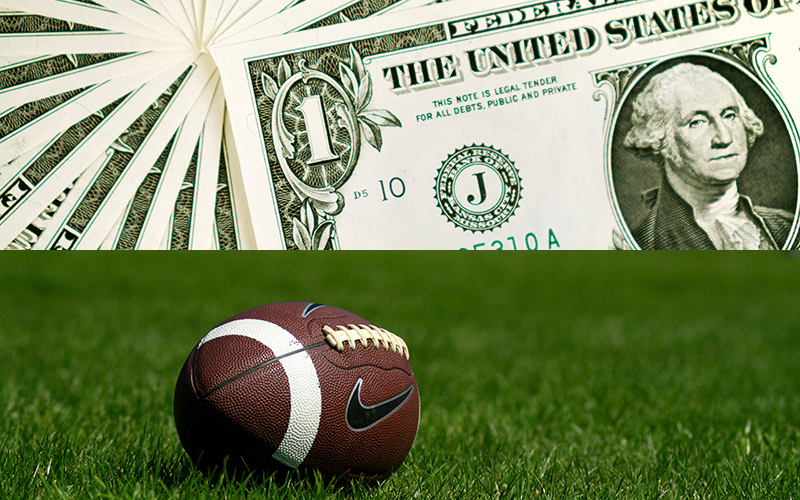 A $1 bill and a football (Photo by Hannah Dickens/ Cronkite News)