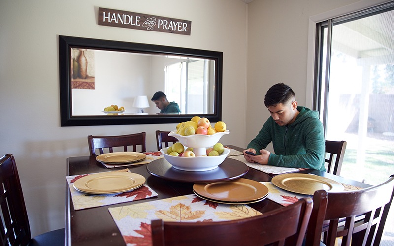 Angel Diaz sits at a table in the home he recently purchased. (Photo by Andres Guerra Luz/Cronkite News)