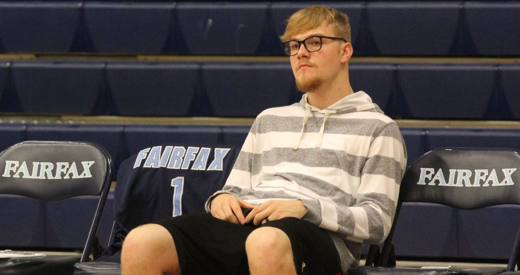 Payton Garrett, injured and unable to play in the first scrimmage, sits alone on the bench next to Isia Slater's jersey. (Photo by Trisha Garcia/Cronkite News)