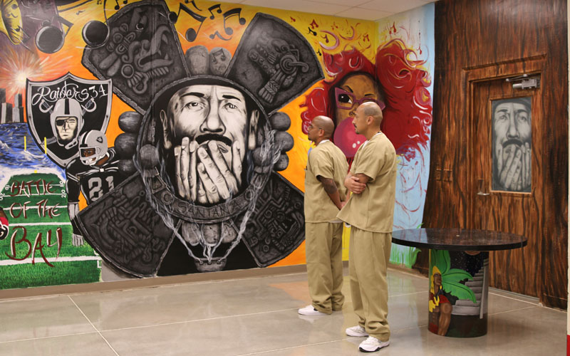 Inmates Andrew Valencia (left) and Juan Ulloa  admire one of their main centerpieces, a mural of musician Carlos Santana. (Photo by Kristiana Faddoul/Cronkite News)
