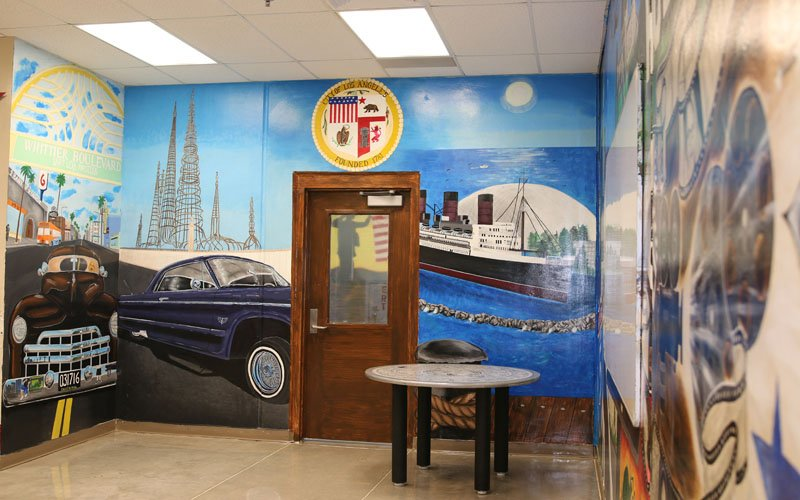 The door of the multipurpose room at La Palma Correctional Center is surrounded by a visual representations of east Los Angeles. (Photo by Kristiana Faddoul/Cronkite News)