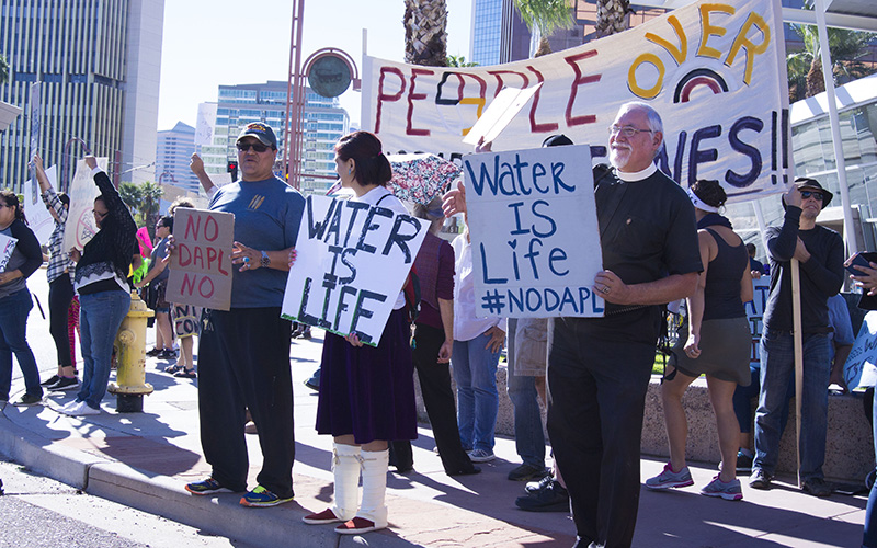Protesters resisting the Dakota Access Pipeline stand with their signs outside of the U.S. Army Corps of Engineers in downtown Phoenix. (Photo by Bri Cossavella/Cronkite News)