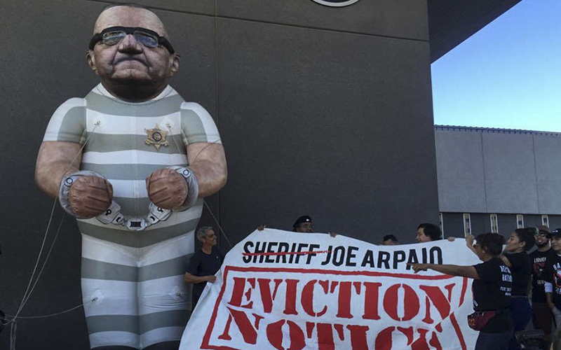 Bazta Arpaio's trademark giant balloon likeness of Joe Arpaio towers over activists at the Maricopa County Sheriff's Office on  Nov. 9, 2016. (Photo by Danielle Quijada/Cronkite News)