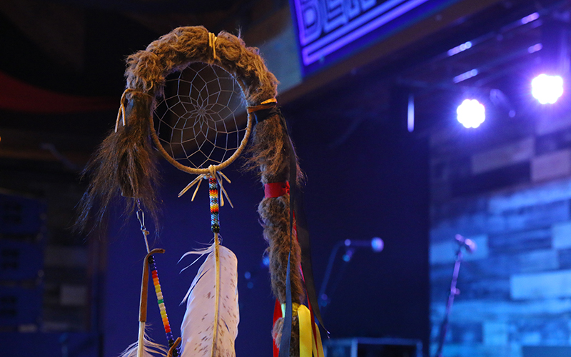 A staff holding a dreamcatcher whose threads symbolized the lives of different animals on earth stood by the stage at a concert in Scottsdale intended to benefit Standing Rock Pipeline protesters on Nov. 13, 2016. (Photo by Andres Guerra Luz/Cronkite News)